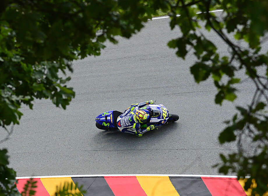 MotoGP World Cup leader and Yamaha rider Valentino Rossi of Italy speeds up during the MotoGP free practice at the Sachsenring circuit in Hohenstein-Ernstthal Germany, Friday, July 10, 2015. The Motorcycle Grand Prix of Germany is scheduled for Sunday. (AP Photo/Jens Meyer)