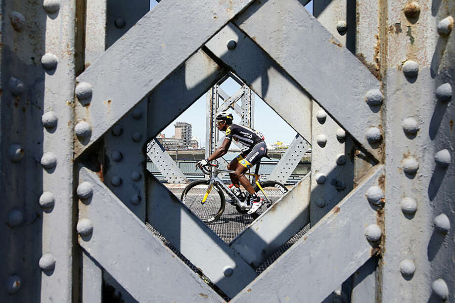 Eritrea's Daniel Teklehaimanot passes over a bridge as he rides in the breakaway group of three riders in Dieppe during the sixth stage of the Tour de France cycling race over 191.5 kilometers (119 miles) with start in Abbeville and finish in Le Havre, France, Thursday, July 9, 2015. (AP Photo/Laurent Cipriani)