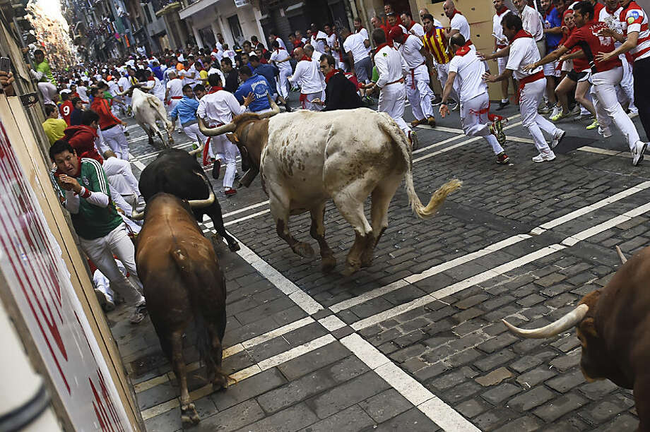 A participant tries to protect himself, left, of ''Fuente Ymbro'' fighting bulls during the fourth running of the bulls, at the San Fermin Festival, in Pamplona, Spain, Friday, July 10, 2015. Revelers from around the world arrive to Pamplona every year to take part in some of the eight days of the running of the bulls. (AP Photo/Alvaro Barrientos)
