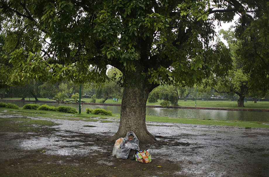 An Indian vendor takes shelter under a tree as it rains in New Delhi, India, Friday, July 10, 2015. India's monsoon season, which runs from June to September, bring rains that are vital to agriculture. (AP Photo/Altaf Qadri)
