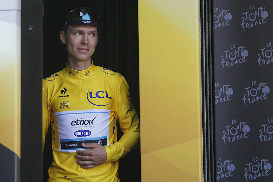 Germany's Tony Martin, wearing the overall leader's yellow jersey, holds his arm in a position which stabilizes his shoulder and collar bone as he arrives on the podium of the sixth stage of the Tour de France cycling race over 191.5 kilometers (119 miles) with start in Abbeville and finish in Le Havre, France, Thursday, July 9, 2015. (AP Photo/Christophe Ena)
