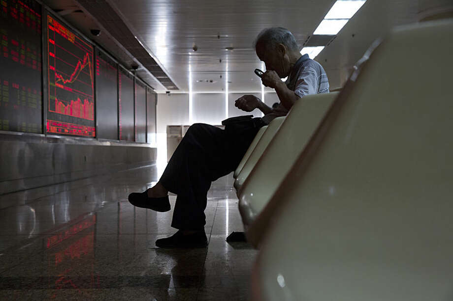 A Chinese stock investor uses a magnifying glass to look at his mobile phone screen as he monitors stock prices at a brokerage in Beijing, China, Thursday, July 9, 2015. Asian stock markets continued to react on Thursday as the Chinese government took measures aimed at stabilizing the market. (AP Photo/Ng Han Guan)