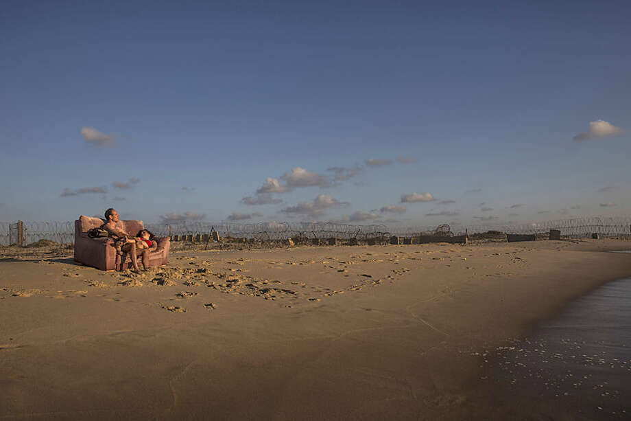 CORRECTS SPELLING OF SECOND NAME TO MENGISTU. In this Saturday, June 20, 2015 photo, Israelis rest by the beach near Kibbutz Zikim, on the Israel-Gaza border. Israeli defense officials say two Israeli citizens are being held in the Gaza Strip. The Israeli defense body responsible for Palestinian civilian affairs, said Avraham Mengistu, born in 1986 from the Israeli city of Ashkelon, independently crossed the border fence into the Gaza Strip in September last year, nearly two weeks after the end of the Israel-Gaza war. The defense body said the second Israeli citizen being held in Gaza is an Israeli of a minority background. It provided no further details about the citizen. (AP Photo/Tsafrir Abayov)