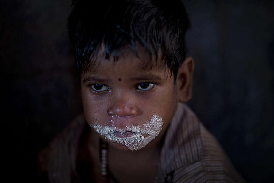 In this June 24, 2015 photo, crumbs of nutritious meal for undernourished children lines the mouth of a boy after he finished eating at a government-run program serving lunch five days a week at Madkheda, Madhya Pradesh state, India. Madhya Pradesh, one of India's largest states is revising school menus to remove an item many devout Hindus found objectionable - eggs. More than half of India's children are malnourished, and nutrition experts say the eggs in school lunches were one of the only means of providing protein to needy kids. (AP Photo/Saurabh Das)