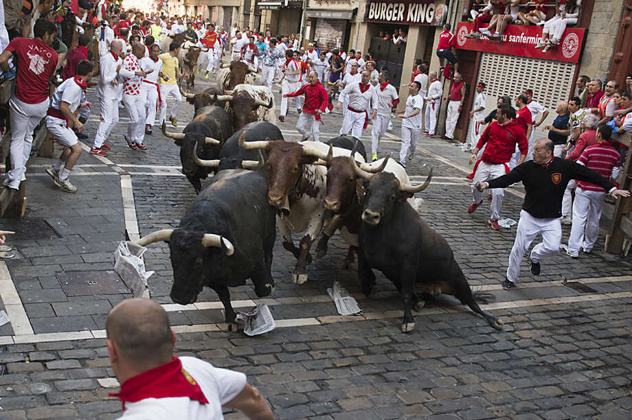 Participants run beside ''Victoriano del Rio Cortes'' fighting bulls along Estafeta corner during the running of the bulls at the San Fermin Festival in Pamplona, Spain, Thursday, July 9, 2015. Revelers from around the world arrive to Pamplona every year to take part in some of the eight days of the running of the bulls. (AP Photo/Alvaro Barrientos)