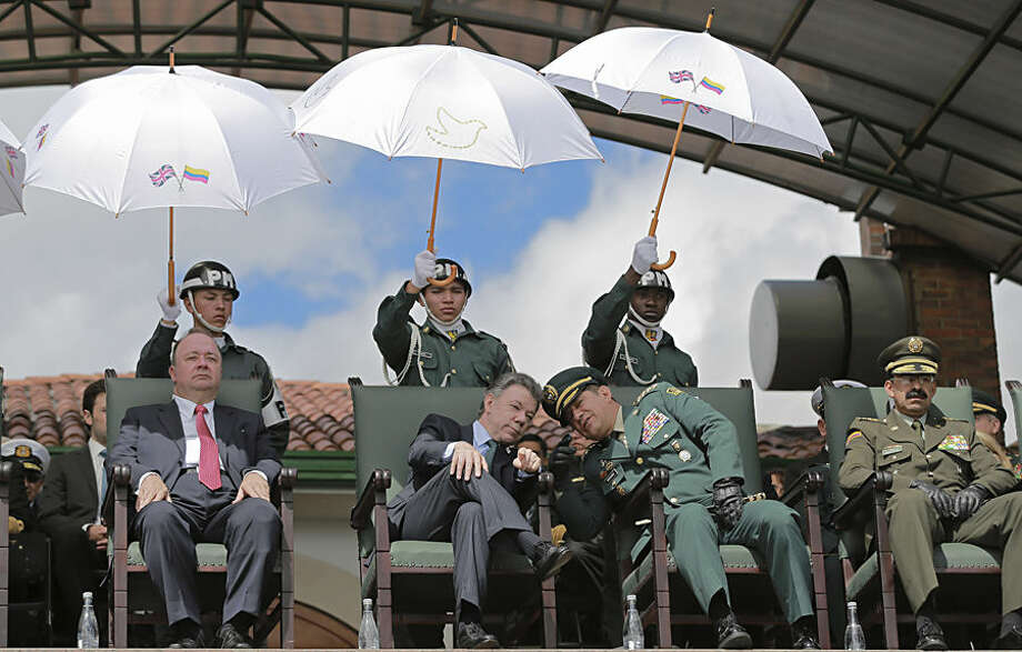 Colombia's President Juan Manuel Santos, center left, leans in to listen to Colombia's Armed Forces Commander Gen. Juan Pablo Rodriguez, during a military ceremony in Bogota, Colombia, Thursday, July 9, 2015. Also pictured are Colombia's Defense Minister Luis Carlos Villegas, left, and Colombia's Police Chief Rodolfo Palomino, right. The event was a swearing-in ceremony for newly named commanders. (AP Photo/Fernando Vergara)