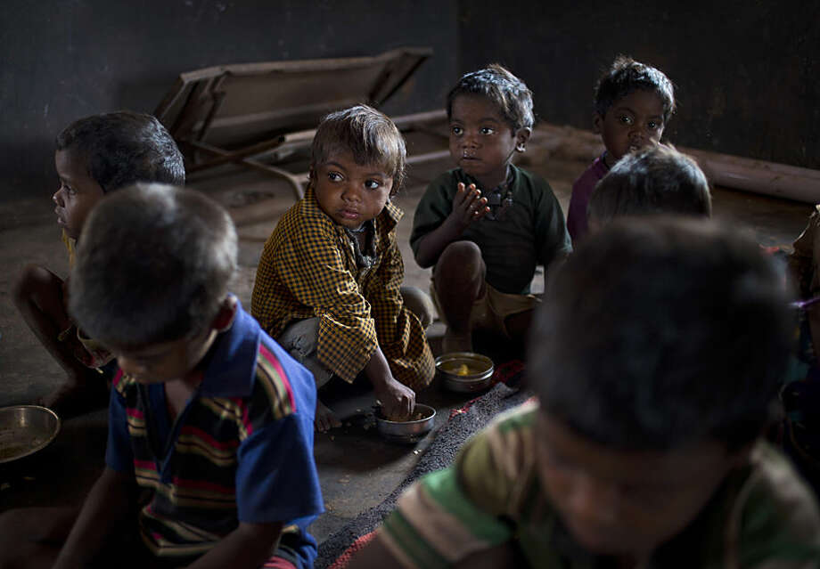In this June 24, 2015 photo, children have a meal of two flatbreads and a scoop of boiled potato curry at a government-run program serving lunch five days a week at Madkheda, Madhya Pradesh state, India. Madhya Pradesh, one of India's largest states is revising school menus to remove an item many devout Hindus found objectionable - eggs. More than half of India's children are malnourished, and nutrition experts say the eggs in school lunches were one of the only means of providing protein to needy kids. (AP Photo/Saurabh Das)