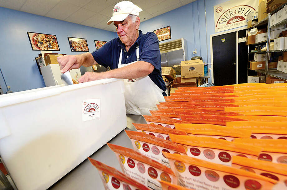 Hour photo / Erik Trautmann Jimmy Kelly packages graola at the family's Norwalk facilty. The Kelly family has been manufacturing Kelly Plus Four Granola in Norwalk for the past 3 years.