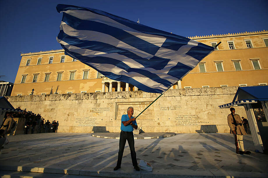 A pro-Euro demonstrator waves a Greek flag in front of the Greek Parliament as riot police, left, block an entrance of a building during a rally at Syntagma square in Athens, Thursday, July 9, 2015. Greece's government is racing to finalize a plan of reforms for its third bailout, hoping this time the proposal will meet with approval from its European partners and stave off a potentially catastrophic exit from Europe's joint currency, the euro, within days. (AP Photo/Petros Karadjias)