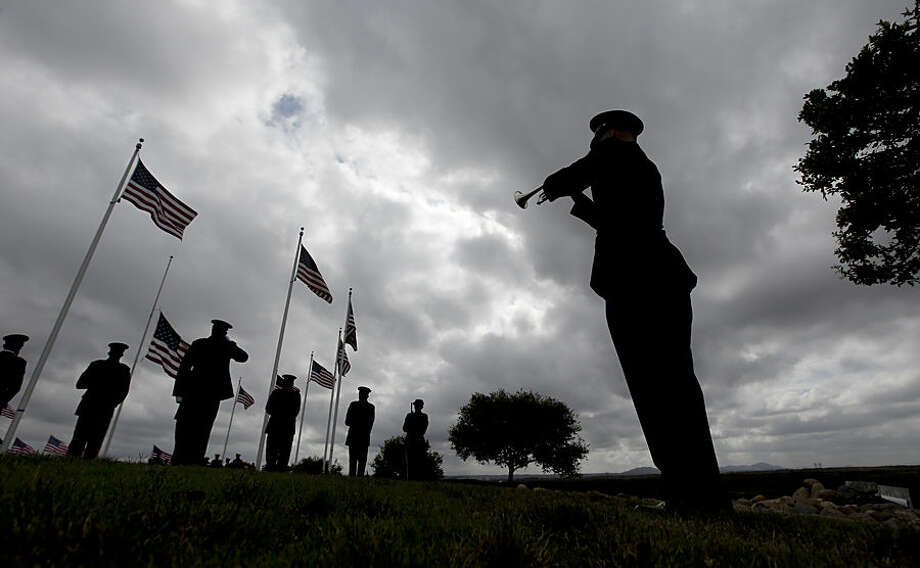 A rifle squad fires a salute at the conclusion of the ceremony as a bugler plays taps for Army Sgt. Charles Schroeter, who was awarded the Congressional Medal of Honor for gallantry in an 1869 battle during the Indian Wars, during a service with full military honors at Miramar National Cemetery, Thursday, July 9, 2015, in San Diego. Schroeter's remains were located only recently, when the Congressional Medal of Honor Historical Society traced them to San Diego's Greenwood Memorial Park, where they had rested since 1921. The remains were interred in an unmarked crypt, along with other unclaimed remains. (AP Photo/Chris Carlson)