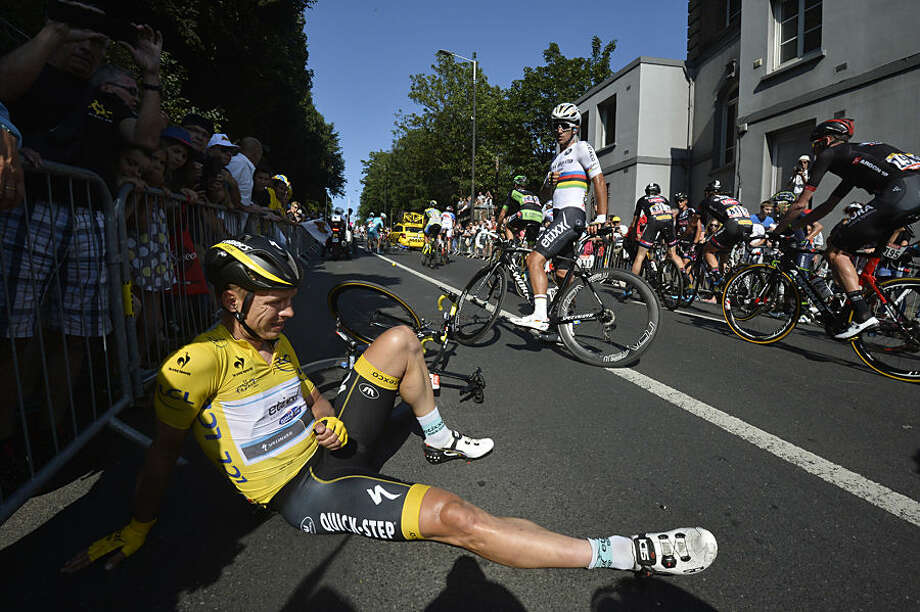 Germany's Tony Martin, wearing the overall leader's yellow jersey, lies on the road with a broken collar bone after crashing in the last kilometers of the sixth stage of the Tour de France cycling race over 191.5 kilometers (119 miles) with start in Abbeville and finish in Le Havre, France, Thursday, July 9, 2015. (AP Photo/Stephane Mantey)
