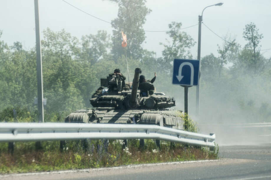 Pro-russian troops ride on a tank on a road in the direction of Donetsk not far from Debaltseve, Donetsk region, eastern Ukraine, Friday, June 20, 2014. (AP Photo/Evgeniy Maloletka)