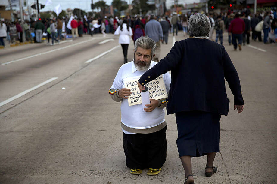 Wilson Franco begs along a street used by people walking to the site where Pope Francis will pass by in his popemobile in Santa Cruz, Bolivia, Thursday, July 9, 2015. After celebrating Mass, Francis' main event of the day is a keynote speech to a summit of grass-roots groups whose advocacy for the poor and marginalized has been championed by history's first Latin American pope. (AP Photo/Rodrigo Abd)