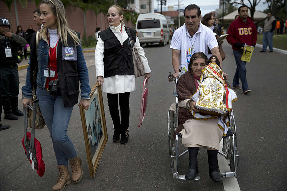 People holding religious icons make their way to Christ the Redeemer square where Pope Francis will celebrate Mass in Santa Cruz, Bolivia, Thursday, July 9, 2015. It's the second day that Francis is visiting Bolivia. He arrived in the Andean nation late Wednesday after spending three days in Ecuador. (AP Photo/Rodrigo Abd)