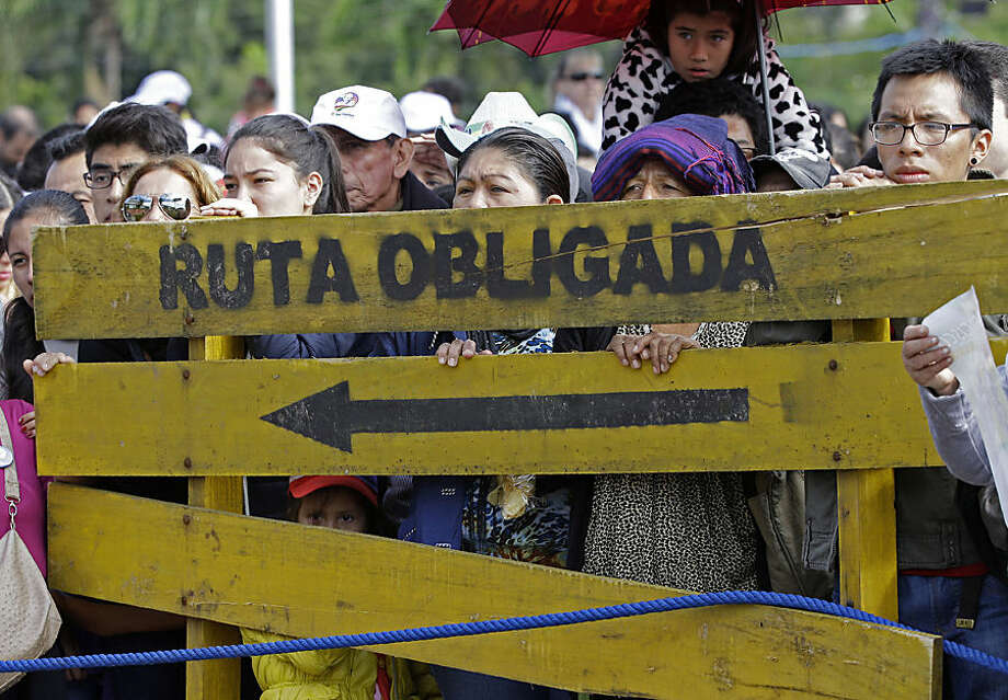 "Faithful stand behind a wooden sign with a message that reads in Spanish; ""Obligatory route"" as they wait for Pope Francis to arrive and celebrate Mass at Christ the Redeemer square in Santa Cruz, Bolivia, Thursday, July 9, 2015. Francis rallied tens of thousands of Bolivians during his first public Mass in Bolivia on Thursday, one of the key days of his South American pilgrimage. (AP Photo/Gregorio Borgia)"