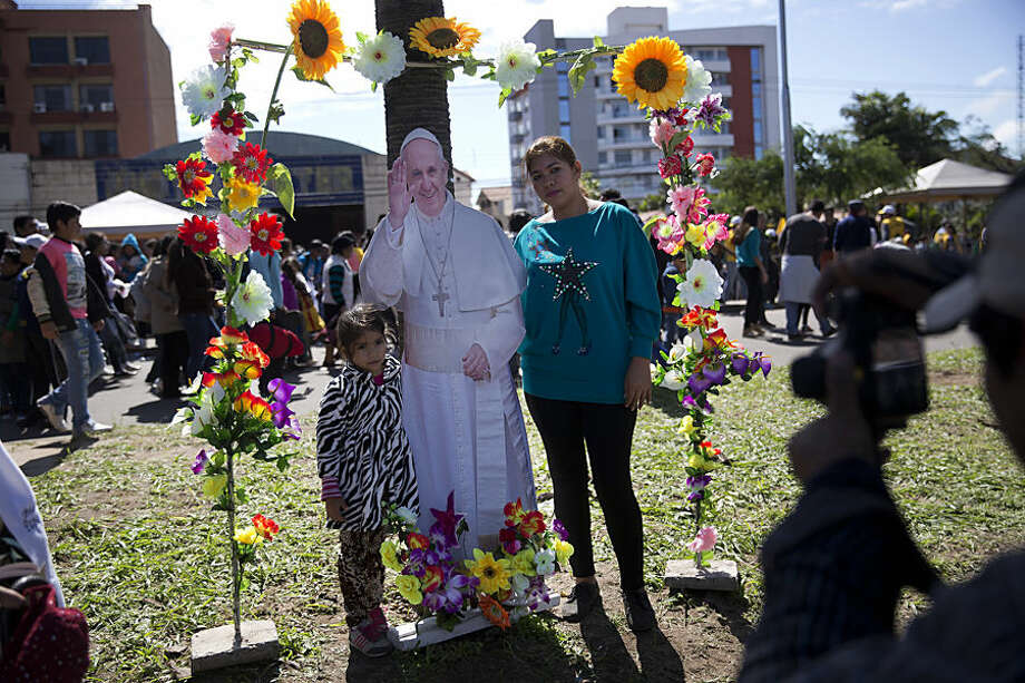A woman and girl pose for a street photographer with a life-size cut out of Pope Francis after the pope celebrated Mass at Christ the Redeemer square in Santa Cruz, Bolivia, Thursday, July 9, 2015. Francis arrived in the Andean nation late Wednesday after three days in Ecuador. (AP Photo/Rodrigo Abd)
