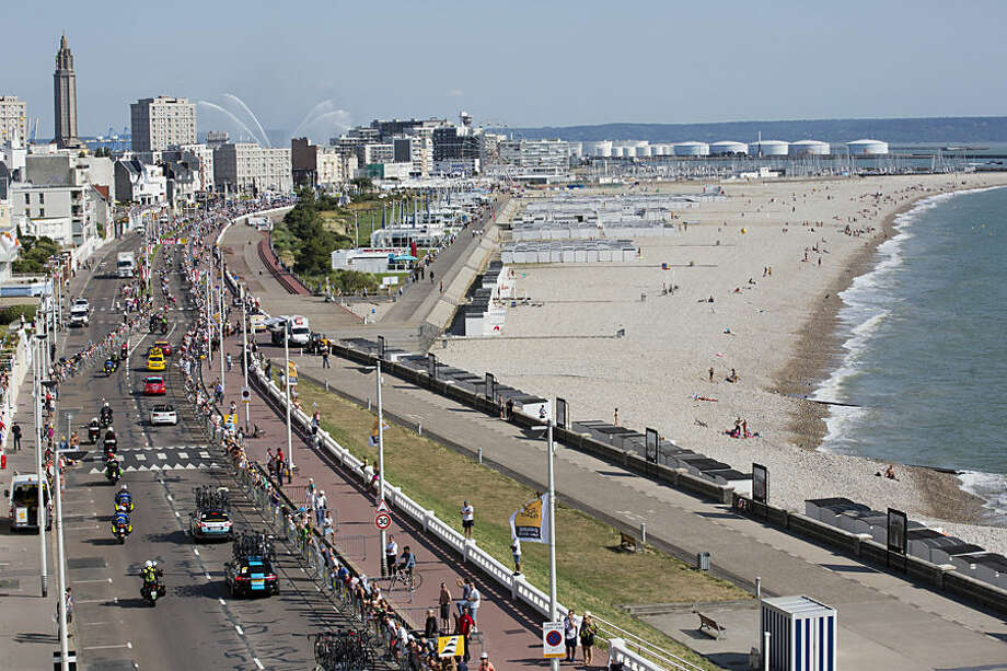 The pack is followed by the team cars as it enters Le Havre during the last kilometers of the sixth stage of the Tour de France cycling race over 191.5 kilometers (119 miles) with start in Abbeville and finish in Le Havre, France, Thursday, July 9, 2015. (AP Photo/Laurent Cipriani)