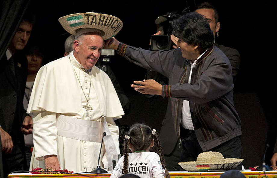 """Bolivia's President Evo Morales places a traditional Bolivian hat on Pope Francis' head during the second World Meeting of Popular Movements in Santa Cruz, Bolivia, Thursday, July 9, 2015. The Pope gave a speech to the delegates at the meeting, a collection of non-governmental organizations representing street sellers, indigenous groups, mining cooperatives and """"cartoneros,"""" who sift through garbage looking for recyclable goods. (AP Photo/Eduardo Verdugo)"""