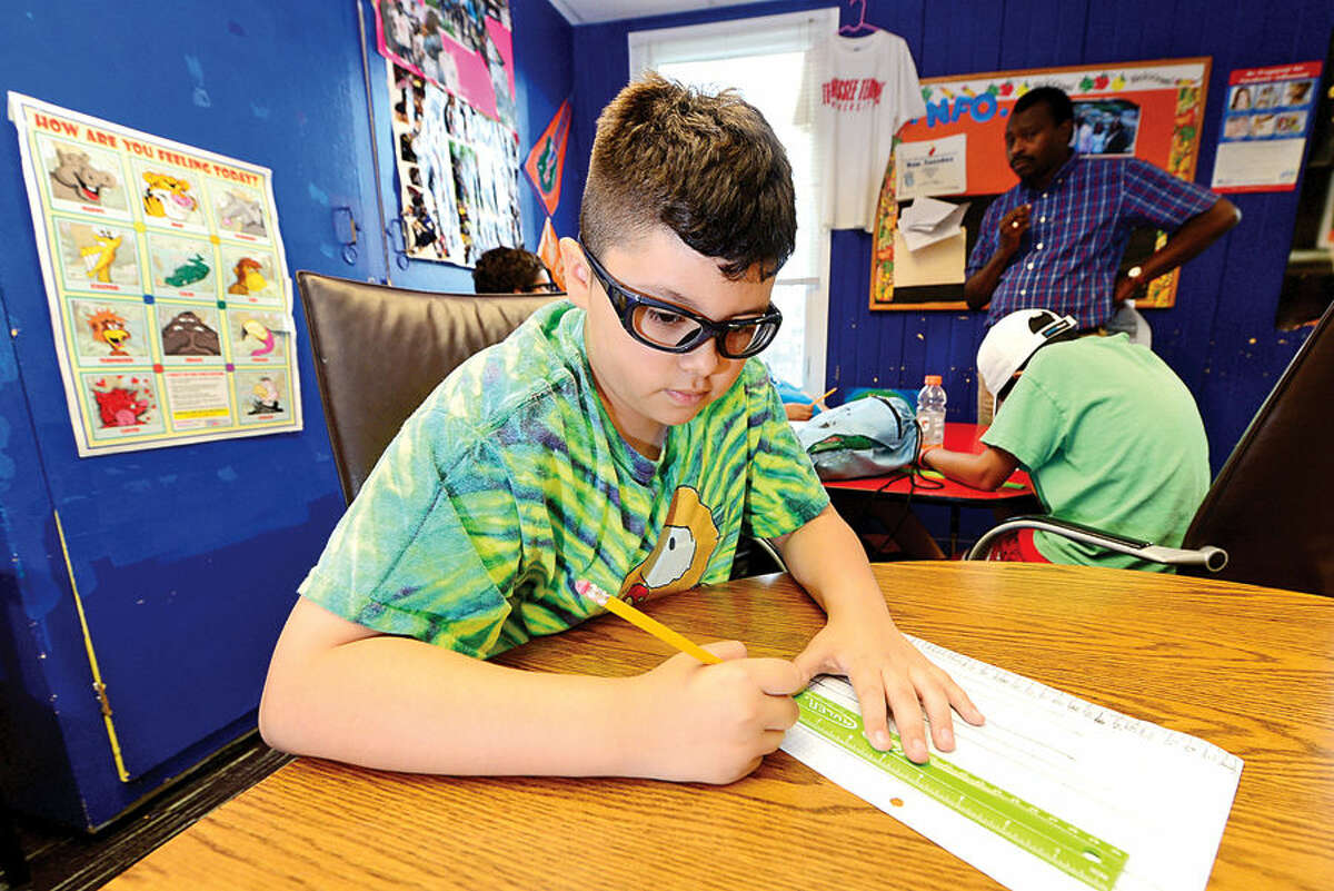 Jonathan Dulcid works on his graph as part of 10-13 year old boys science program at the Carver Community Center as part of the Carver Foundation's summer camps.