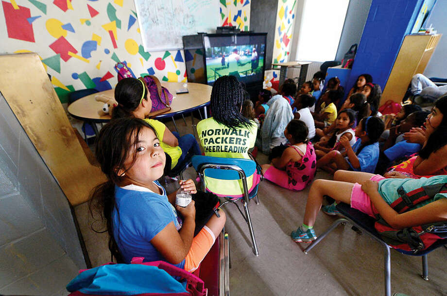 Hour photo / Erik Trautmann Michelle Carreno, 7, enjoys movie time at the Carver Community Center Tuesday as part of the Carver Foundation's summer camp programs.