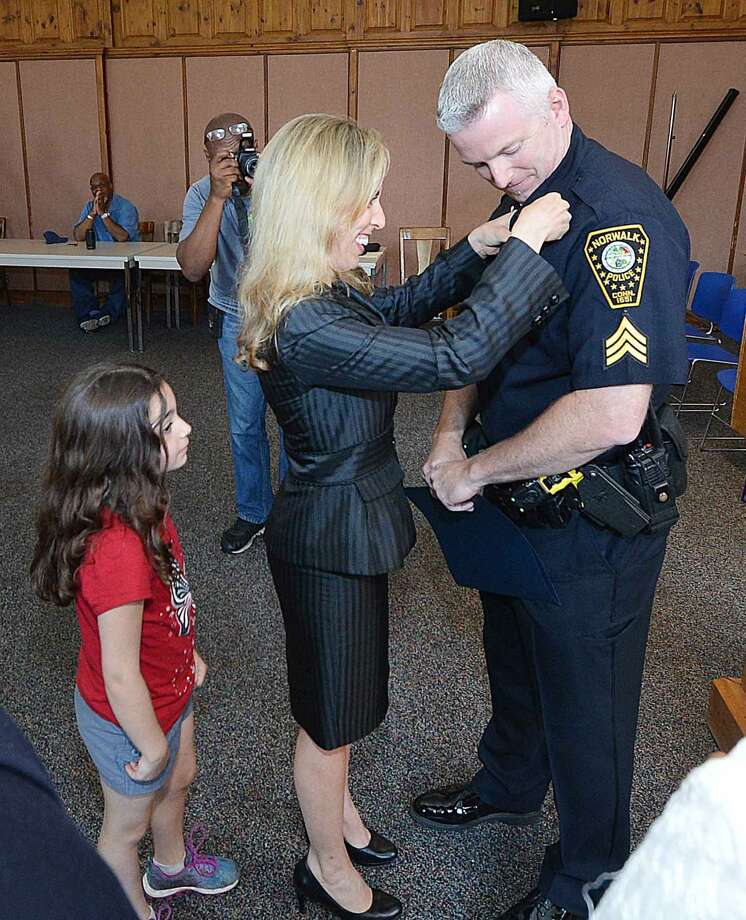 Hour Photo/Alex von Kleydorff Terry Blake has his badge pinned on by wifeTracy Dayton and daughter Jillian Blake