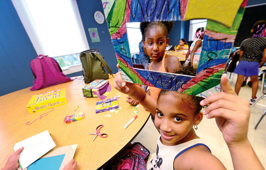 Hour photo / Erik Trautmann Cyarah Thomas, 9, and Ayah Johnson, 7, make picture frames during the girls art program at the Carver Community Center Wednesday as part of the Carver Foundation's summer camps.