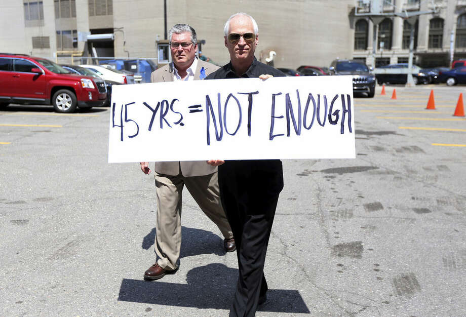 Daniel Chevalier, right, holds a sign in support of his friend Jeff Bere, left, who lost his father to cancer, as victims and victim survivors gathered outside the Theodore Levin United States Courthouse in Detroit, Friday, July 10, 2015, after the sentencing of Dr. Farid Fata, 50 of Oakland Township to 45 years in prison for his role in a healthcare fraud scheme along with unnecessary treatment to 553 individual patients. (Todd McInturf/Detroit News via AP)
