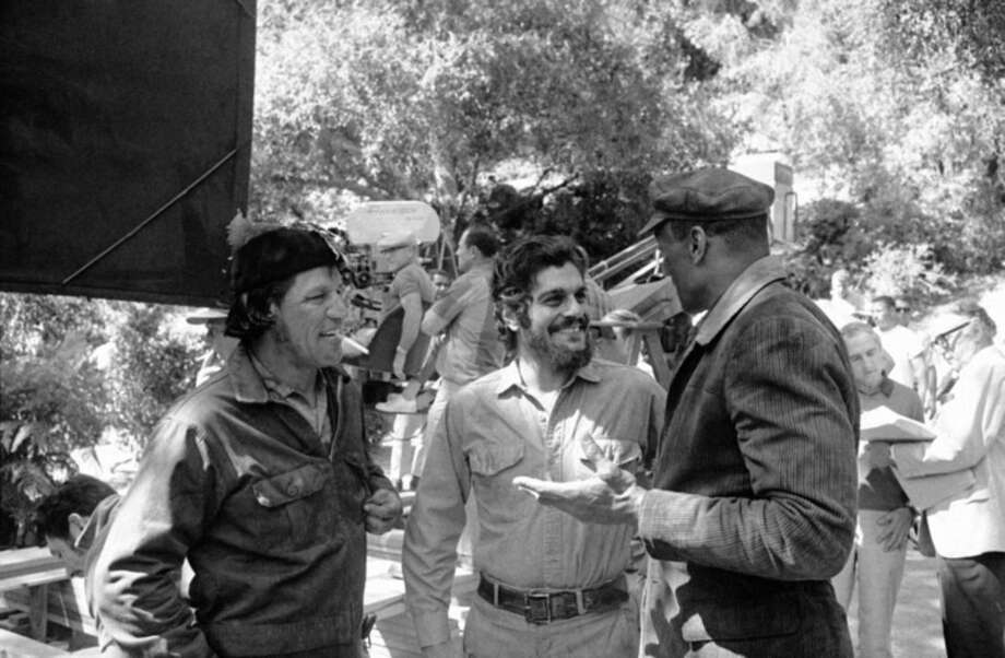 FILE - In this Sept. 23, 1968 file photo, actor Omar Sharif, center, playing the role of the Cuban revolutionary Ernesto (Che) Guevra, takes a break from filming in Hollywood. With Sharif are Rudy Diaz, left, former Los Angeles policeman, and former football player Woody Strode, both of whom play the parts of members of Che?s guerilla band. Sharif has died in a Cairo hospital of a heart attack, his agent said on Friday, July 10, 2015.(AP Photo/Harold Filan, File )