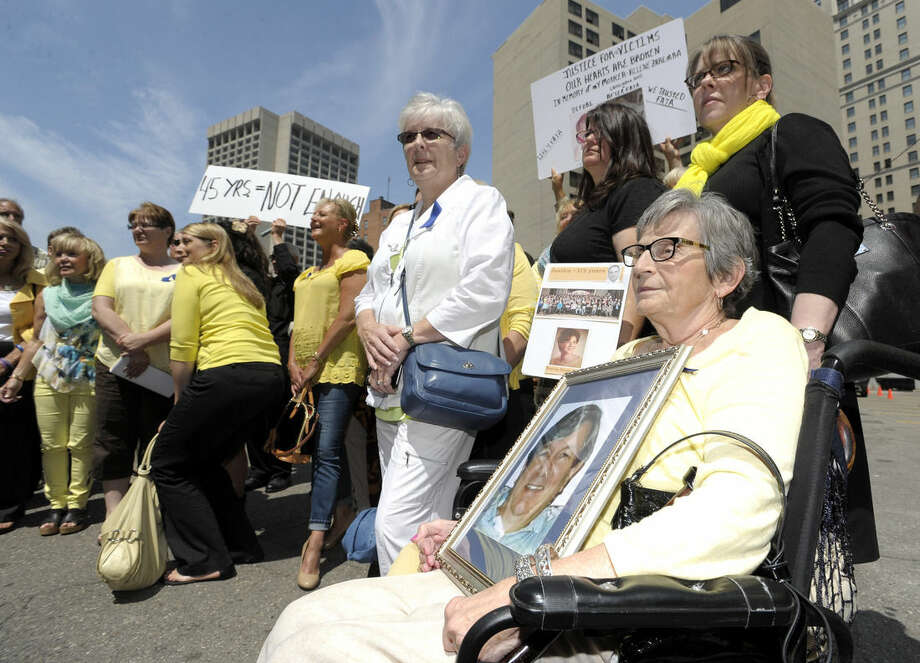 Pat Steinhelper, right, 77, of Waterford, holds a picture of her husband, Jerry Steinhelper, who died due to complications of chemotherapy at the hands of Dr. Fata. She poses for a group shot with other victims and victims family members after the sentencing. Victims and the family members of victims are emotional as they leave the federal courthouse in Detroit, Friday, July 10, 2015, after they listen to the 45-year sentencing of Dr. Farid Fata for misdiagnosis of cancer and Medicare fraud. (Todd McInturf/Detroit News via AP)