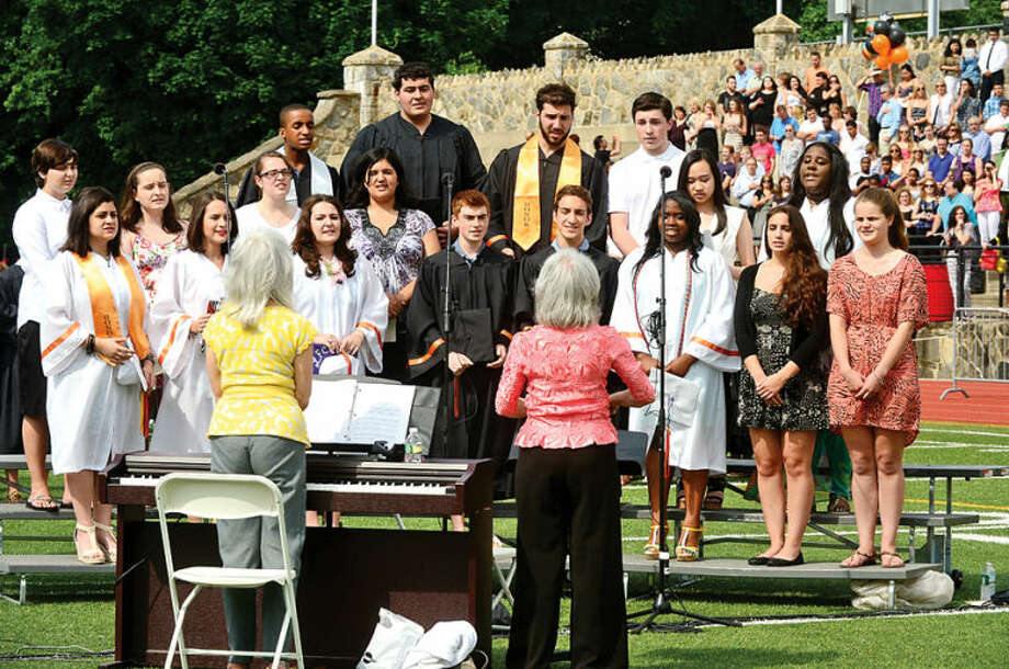 Hour photo / Erik Trautmann The Stamford High School Concert Choir and Madrigal Singers sing The National Anthem during commencement exercises for the Class of 2014 Thursday afternoon at Boyle Stadium.