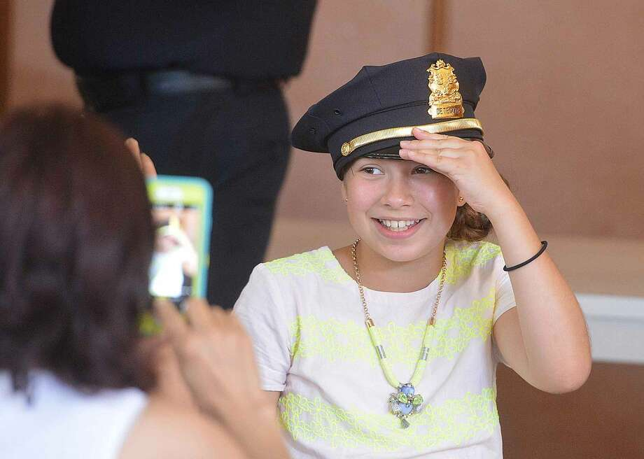 Hour Photo/Alex von Kleydorff 11 yr old Isabel Gonzalez puts on her Uncle Ashley Gonzalez's cap before the police promotion ceremony where he was promoted to Norwalk Police Department Deputy Chief