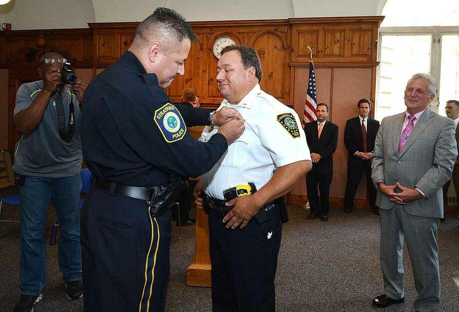 Hour Photo/Alex von Kleydorff Stratford Police Detective Heineman Gonzalez pins the Deputy Chief badge on his brother Ashley Gonzalez during a promotion ceremony at City Hall