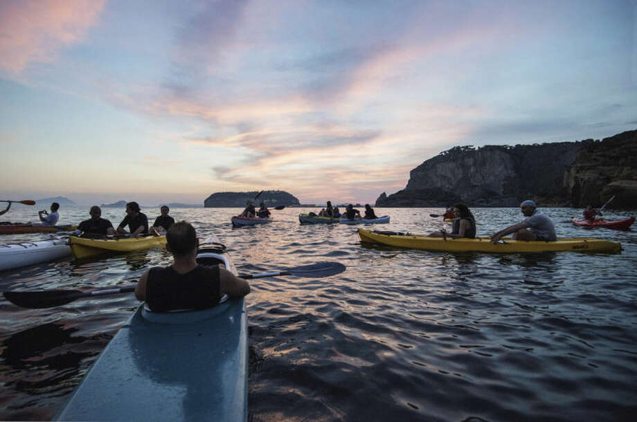 In this Friday, June 13, 2014 photo, tourists enjoy a sunset kayak tour along the Posillipo coastline, in Naples, Italy. Three years ago Naples' seafront was an urban highway, noisy and smoggy, jammed with car traffic, while smelly trash erupted from garbage bins along streets and alleys. Urban cyclers were regarded as eco-fundamentalists. Three years later, Naples has a new mayor, clean streets, a wide pedestrian beachfront and a 20-kilometer (20-mile) cycling lane overlooking a beautiful bay. (AP Photo/Salvatore Laporta)