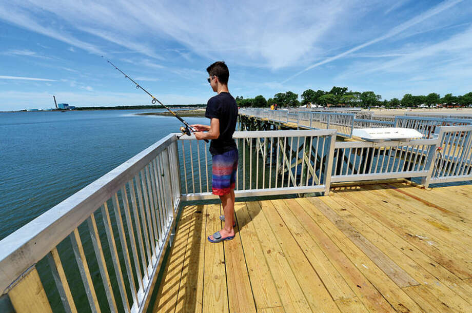 Hour photo / Erik Trautmann Anthony Horicka takes adavantage of the new fishing pier at Calf Pasture Beach that is now open to the public. New amenities include benches and fish cleaning stations.