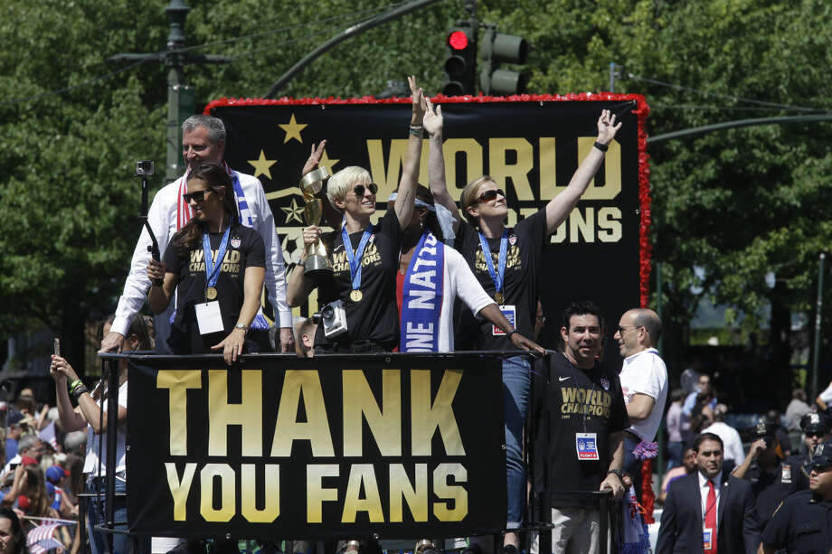 U.S. women's soccer team midfielder Megan Rapinoe, center, holds up the World Cup trophy as midfielder Carli Lloyd, left, New York City Mayor Bill de Blasio, left background, and head coach Jill Ellis, right, wave to the crowd as their float makes it way up Broadway's Canyon of Heroes during the ticker tape parade to celebrate the U.S. women's soccer team World Cup victory, Friday, July 10, 2015, in New York. (AP Photo/Mary Altaffer)