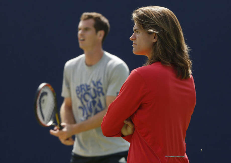 """ADVANCE FOR WEEKEND EDITIONS, JUNE 21-22 - FILE - In this June 12, 2014, file photo, Andy Murray's new coach Amelie Mauresmo, right, watches him practice during a training session before his Queen's Club grass court championships tennis match in London. The pairing of defending champion Andy Murray and his new coach, Amelie Mauresmo, was quickly dubbed """"Murresmo,"""" and their partnership is sure to draw a lot of notice. (AP Photo/Sang Tan, File)"""