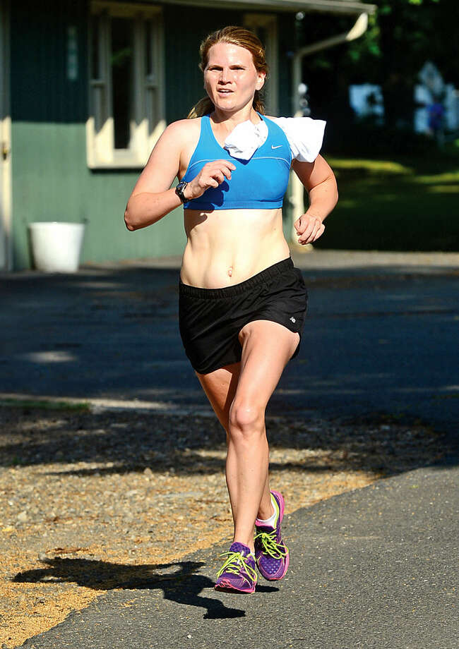 Hour photo / Erik Trautmann Kate Pfeffer finishes first for the women in the 3.1 mile race during the Westport Road Runners Summer Series Saturday at Longshore Park.