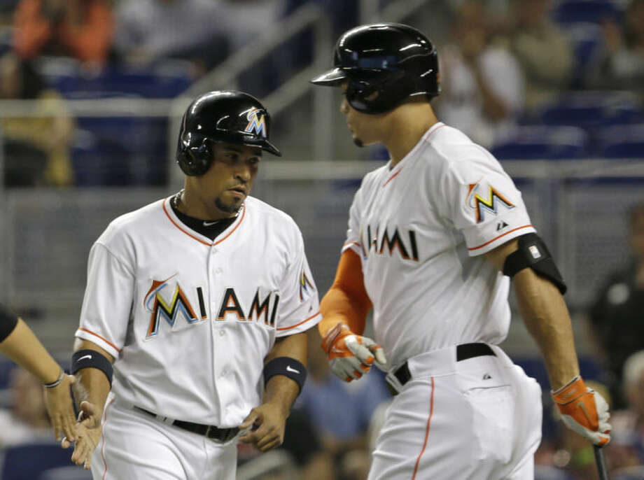 Miami Marlins' Rafael Furcal, left, is congratulated by teammate Giancarlo Stanton, right, after scoring on a ground ball hit by Adeiny Hechavarria against the New York Mets in the first inning of a baseball game in Miami, Friday, June 20, 2014. (AP Photo/Alan Diaz)