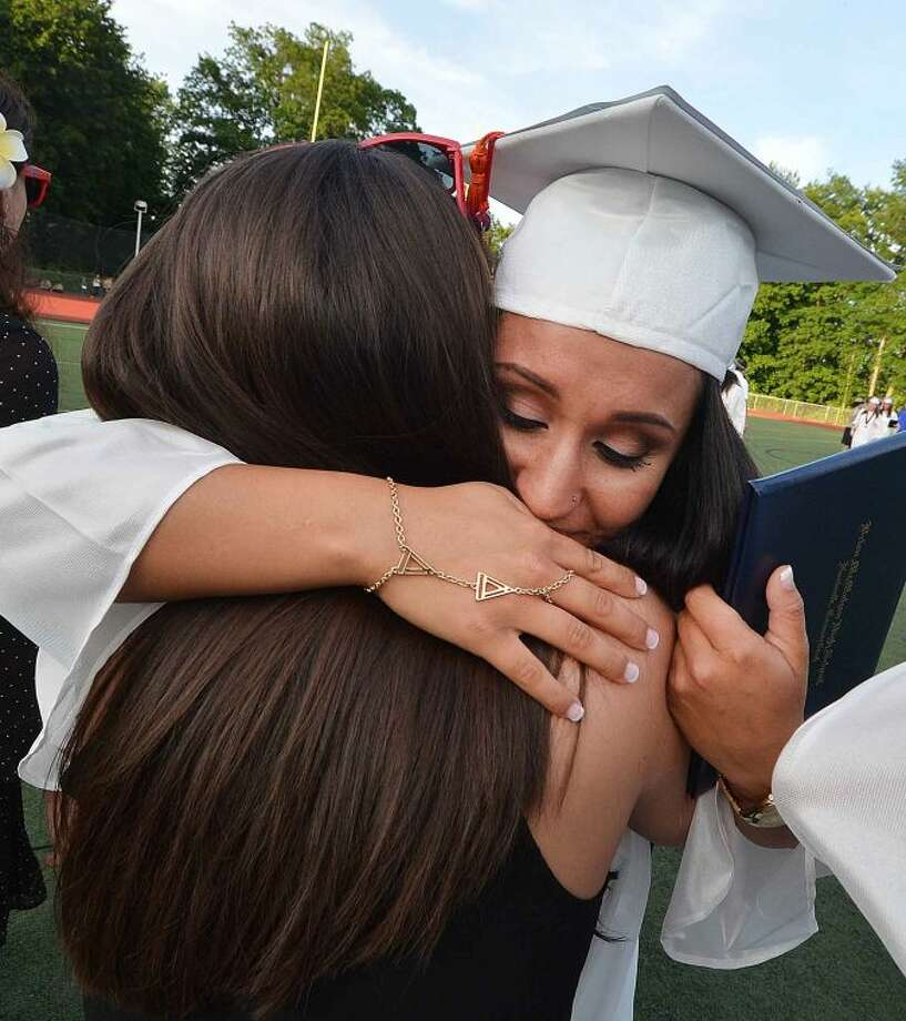 Hour Photo/Alex von Kleydorff Alyssia Gonzalez gets a long hug from her teacher Laura Quagliata as she graduates with the Brien McMahon Class of 2014 Graduation