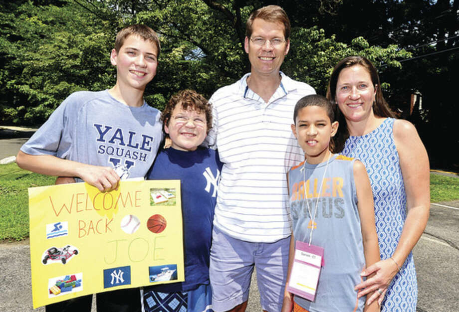 Hour photo/Erik TrautmannThe Baylis family, -- Charlie, Andrew, John and Jessica -- greet Joe Luis Garcia as The Fresh Air Funds Southwest Coast, CT, Committee welcomes children from New York City as they arrive in Darien Saturday to spend one or two weeks with volunteer host families in Norwalk, Wilton, Darien, Ridgefield, and New Canaan.