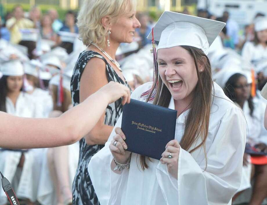 Hour Photo/Alex von Kleydorff Jenny Raymond shows off her diploma in hand as she graduates with the Brien McMahon Class of 2014