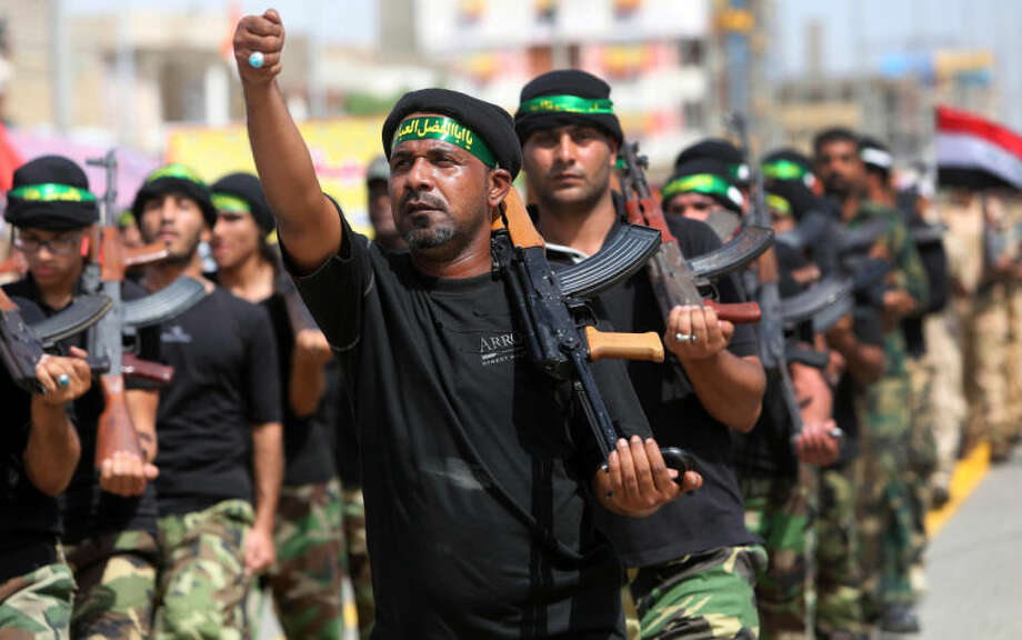 """Volunteers of the newly formed """"Peace Brigades"""" participate in a parade in Basra, Iraq's second-largest city, 340 miles (550 kilometers) southeast of Baghdad, Iraq, Saturday, June 21, 2014. The armed group was formed after radical Shiite cleric Muqtatda al-Sadr called to form brigades to protect Shiite holy shrines against possible attacks by Sunni militants. (AP Photo/Nabil Al-Jurani)"""