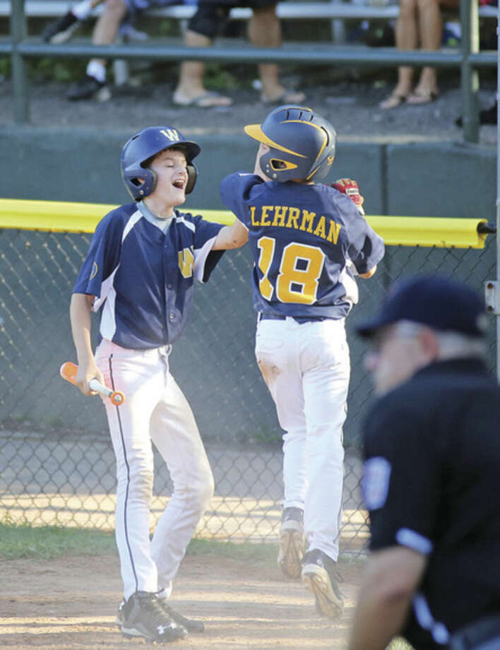 Hour photo/Danielle CallowayWeston's Alexander Olsen, left, congratulates teammate Myles Lehrman after they both crossed home plate during Friday's District 1 Little League game against Ridgefield at Springdale Field in Stamford.