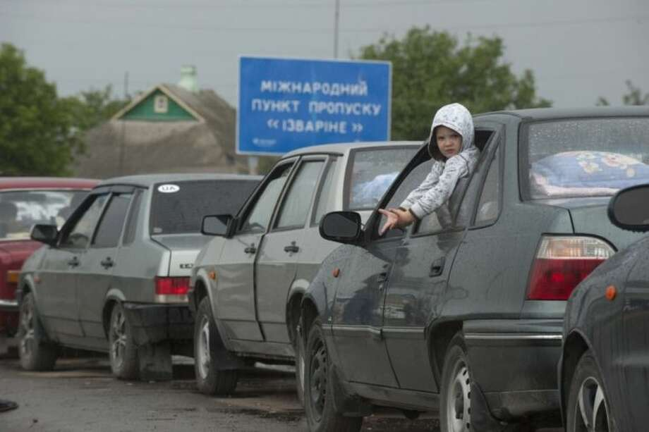 A child sits in a car standing in line to cross the border into Russia at the Ukrainian-Russian border checkpoint in Izvaryne, eastern Ukraine, Friday, June 20, 2014. Some Ukrainians are leaving amid fighting in eastern Ukraine. Clashes between government forces and pro-Russia rebels flared ahead of the publication of a presidential peace plan that includes a unilateral cease-fire. A poster in the background reads International border checkpoint Izvaryne. (AP Photo/Evgeniy Maloletka)