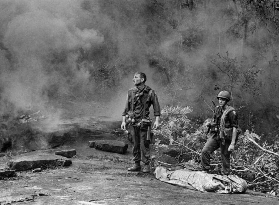 """ADVANCE FOR USE SUNDAY, JUNE 22, 2014, AND THEREAFTER - FILE - In this Aug. 14, 1966 file photo, U.S. Army soldier Ruediger Richter gazes aloft as a helicopter prepares to land to pick up the body of a fallen soldier killed by mortar fire in South Vietnam. Taken by an Army photographer and transmitted worldwide by The Associated Press, the image came to be known widely as """"The Agony of War."""" Richter, a native of Germany who joined the U.S. military after serving in the French Foreign Legion, was part of the 4th Battalion, 503rd Infantry, 173rd Airborne Brigade at the time. He was severely wounded the following year and later developed addictions to alcohol and pain medications while struggling with an undiagnosed case of post-traumatic stress syndrome. After returning to Europe and living in Germany and Hungary with his second wife, Richter moved back to the United States a few years ago received medical care. He now lives in peace in a rural area near Columbus, Georgia. (AP Photo/U.S. Army, Pfc. L. Paul Epley, File)"""