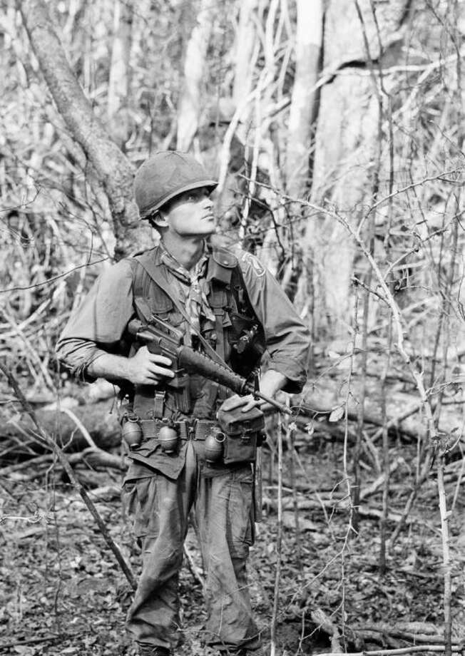 FILE - In this 1966 file photo, Berlin-born paratrooper Ruediger Richter patrols in the jungle northeast of what is now called Ho Chi Minh City as a member of the U.S. Army's 4th Battalion, 503rd Infantry, 173rd Airborne Brigade. As a boy, Richter saw bodies in the streets of Hitler's Germany, where he spent his childhood. He then became a professional killer, first as a member of the French Foreign Legion and later as a member of the U.S. Army. A gunshot through the head ended his Vietnam combat service in 1967, leaving him with a shattered face and a heart hollowed out by anger and addictions. He has since found his peace living in the rural Southern United States near Columbus, Georgia. (AP Photo/Henri Huet, File)