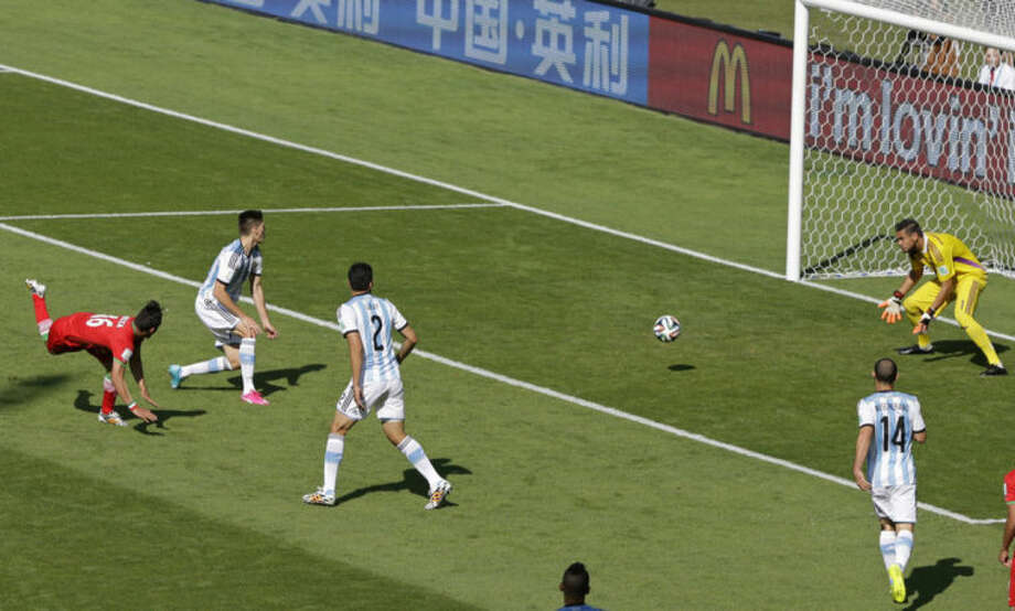 Argentina's goalkeeper Sergio Romero. right, blocks the ball after a header from Iran's Reza Ghoochannejhad during the group F World Cup soccer match between Argentina and Iran at the Mineirao Stadium in Belo Horizonte, Brazil, Saturday, June 21, 2014. (AP Photo/Sergei Grits)