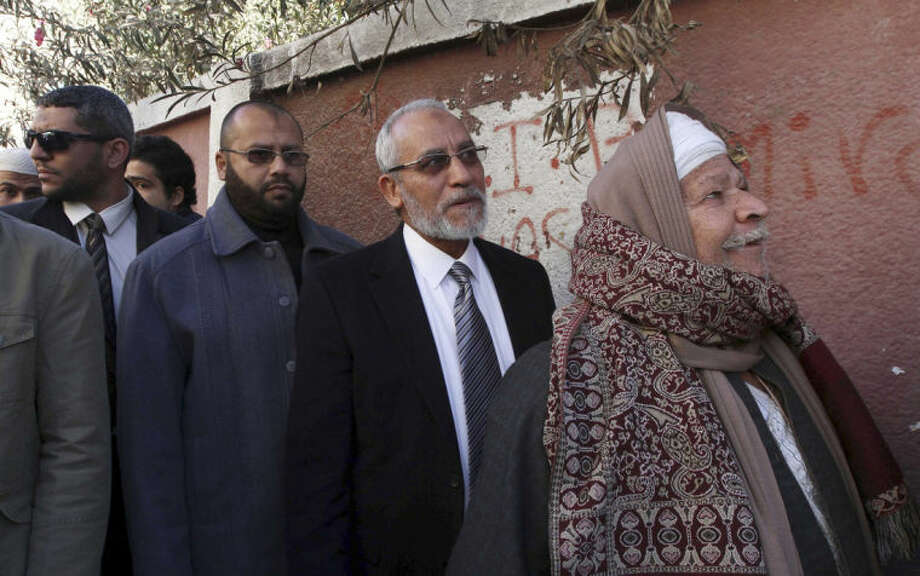 FILE - In this Saturday, Dec. 22, 2012 file photo, Muslim Brotherhood leader Mohammed Badie, second right, waits in line outside a polling place in Beni Suef, Egypt, to vote on a constitution drafted by Islamist supporters of President Mohammed Morsi. Badie, the Muslim Brotherhood's spiritual leader and over 180 others were sentenced to death Saturday, June 21, 2014 by an Egyptian court in the latest mass trial following last year's overthrow of the country's Islamist president. The ruling by the southern Minya Criminal Court is the largest confirmed mass death sentence to be handed down in Egypt in recent memory and comes from Judge Said Youssef, who earlier presided over the mass trial. It is the second death sentence for Badie since the crackdown against his group began. (AP Photo/Ahmed Ramadan, File)