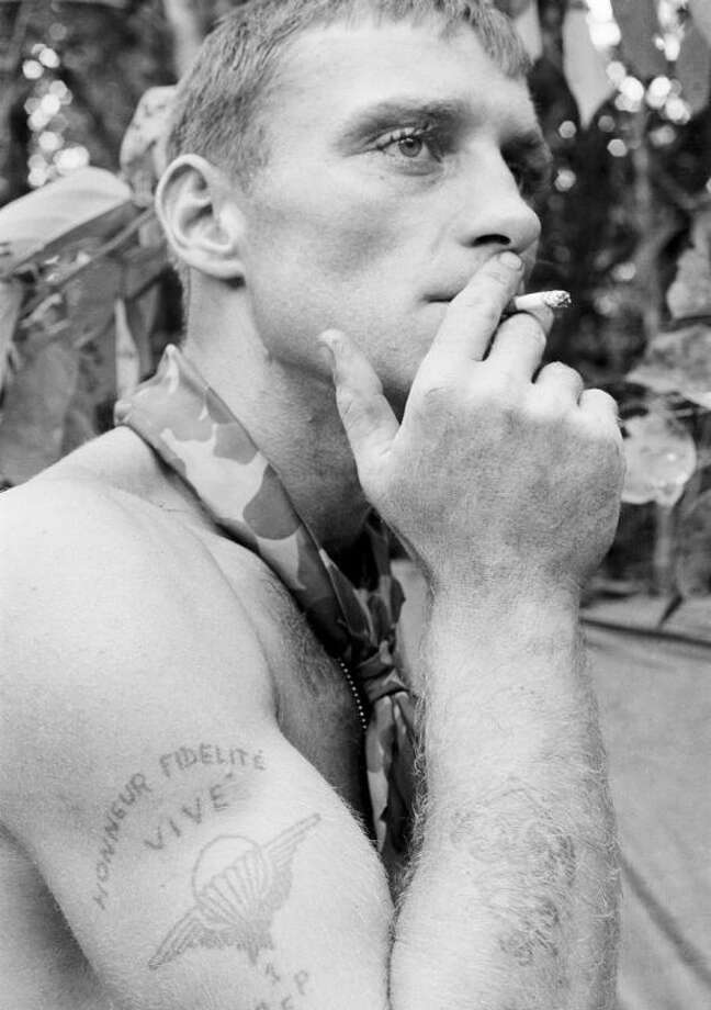 """FILE - In this 1966 file photo, U.S. Army soldier Ruediger Richter puffs on a cigarette in a South Vietnamese jungle during his service in the Vietnam War. The picture of the Berlin native was taken within days of Richter's image being captured in a photo that came to be known as """"The Agony of War."""" Richter was severely wounded by a gunshot through the head the following year and then struggled with anger, addictions and post-traumatic stress syndrome for decades. Now a 73-year-old grandfather, Richter lives with his wife in peace in the rural Southern United States near Columbus, Georgia. (AP Photo/Henri Huet, File)"""