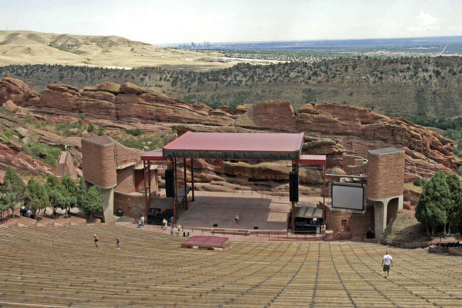 FILE -- This Aug. 13, 2008 file photo shows Red Rocks Amphitheater with the city of Denver in the distance. Law enforcement officers were searching for a gunman Friday, June 20, 2014, after three people were shot and wounded in the parking at the end of a rap concert Thursday night at the popular outdoor amphitheater in the foothills west of Denver. The victims' injuries were not life-threatening, Jefferson County sheriff's spokesman Mark Techmeyer said. Their names were not released. (AP Photo/Ed Andrieski, FILE)